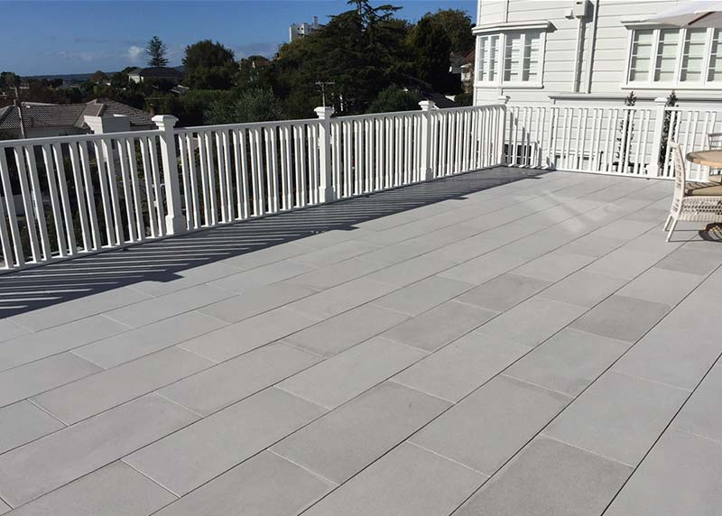 This balcony has rectangle concrete paving stones Installed offset on nurajacks