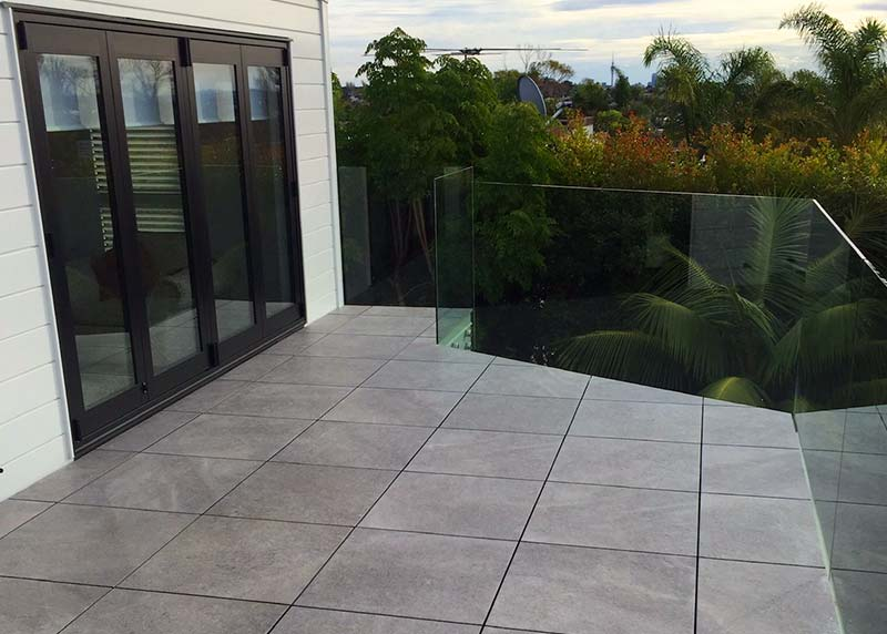 Exterior structural tiles on pedestals make a solid deck. The glass balustrade provide an uninterrupted view
