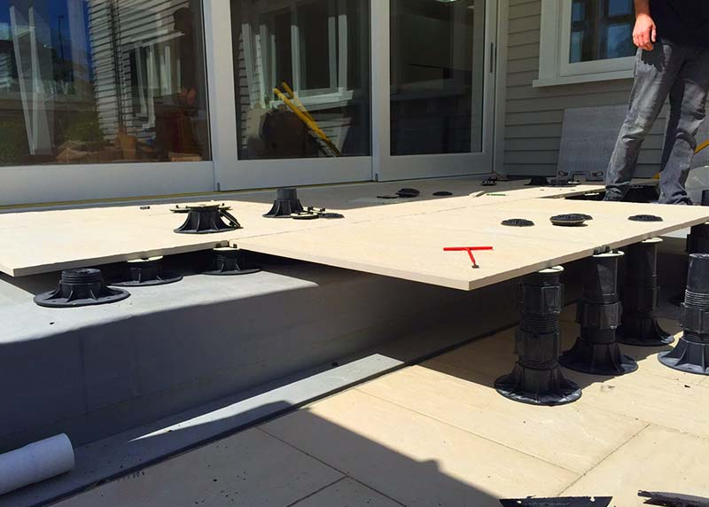 Exterior structural tiles on nurajack pedestals create a level deck from the house and cover over a large step