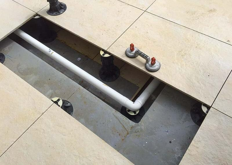 Structured tiles on pedestals are removable and allow subfloor inspection of membranes, drains and water services.