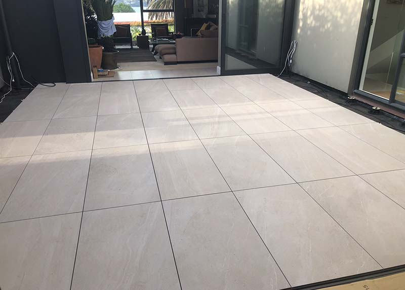 Deck tile installation in a courtyard, rectangular tiles elongate an enclosed space
